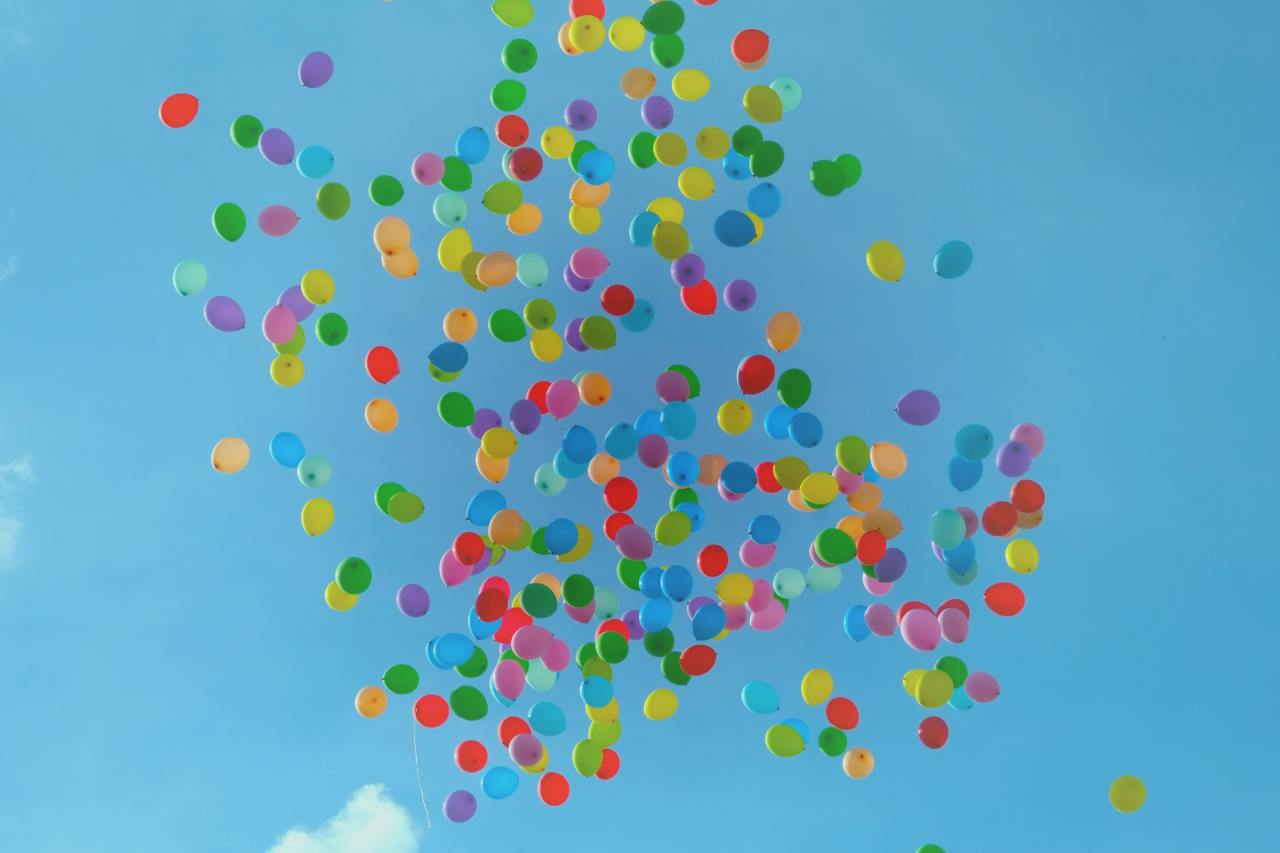 Colorful balloons floating away in the sky.
